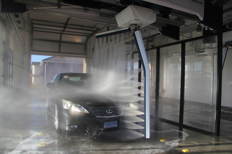 an automobile automatically washes with spraying water from multiple ...